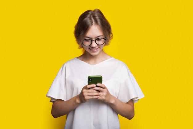 Une femme souriante avec des lunettes et des cheveux blonds discute sur un mobile posant sur un mur de studio jaune