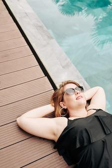 Femme souriante à lunettes de soleil au bord de la piscine de l'hôtel spa, vue d'en haut
