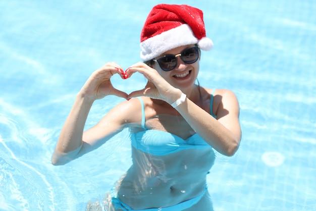 Une femme souriante à lunettes de soleil et un chapeau de père noël montre un geste cardiaque en se tenant debout dans la piscine