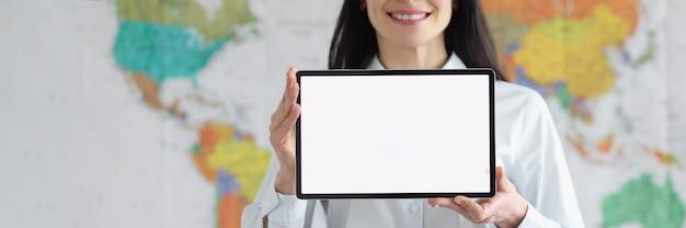 Une femme souriante à lunettes tient une tablette avec un écran blanc blanc sur fond de carte globale du monde