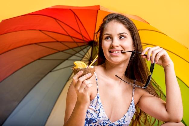 Femme souriante en maillot de bain avec boisson