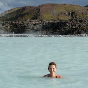Femme souriante en maillot de bain immergé dans une piscine minérale géothermique