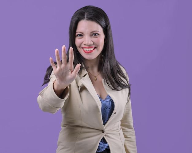 Femme souriante avec la main tendue montrant cinq
