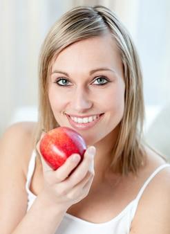 Femme souriante mangeant une pomme