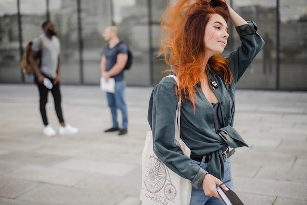 Femme souriante marchant avec un livre