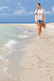 Femme souriante et marchant sur la plage contre la mer