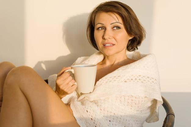 Femme souriante mature assise à la maison sur une chaise