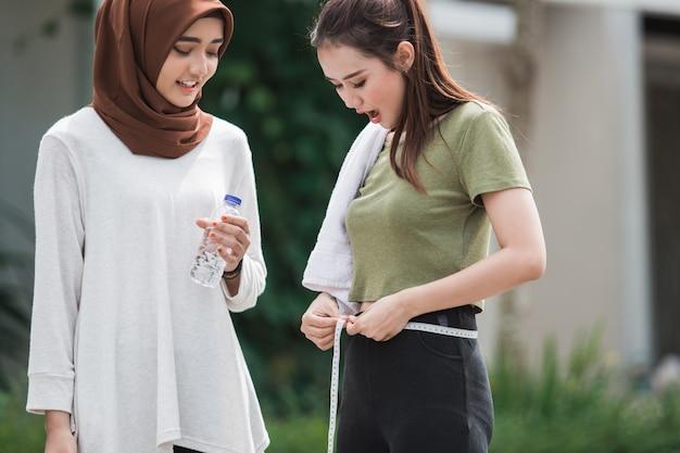 Femme souriante mesurer son ventre après l'exercice