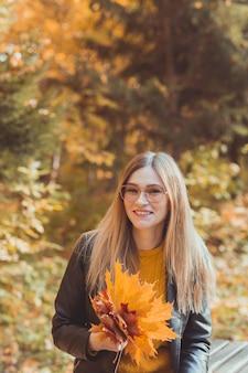 Femme souriante mignonne tenant des feuilles d'automne dans le parc d'automne. concept saisonnier, style de vie et loisirs.