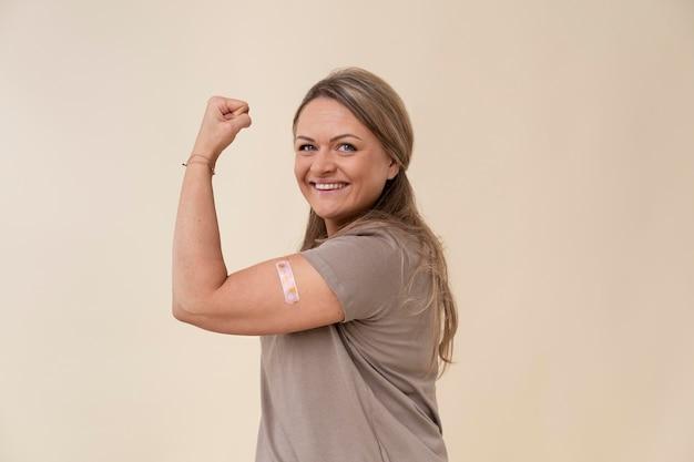 Femme souriante montrant des biceps avec un autocollant après avoir reçu un vaccin