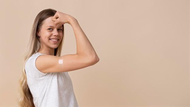 Femme souriante montrant le bras avec un autocollant après avoir reçu un vaccin