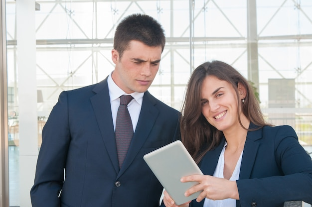 Femme souriante montrant les données de l'homme concentré sur tablette