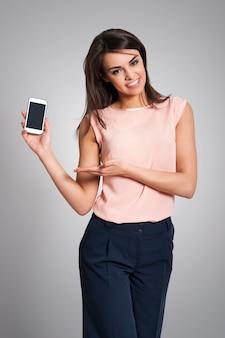 Femme souriante montrant l'écran du téléphone mobile contemporain
