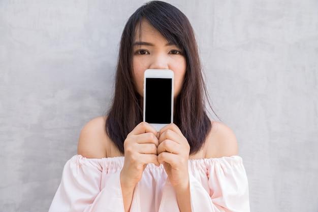 Femme souriante, montrant un écran de smartphone vide debout sur le mur de béton.