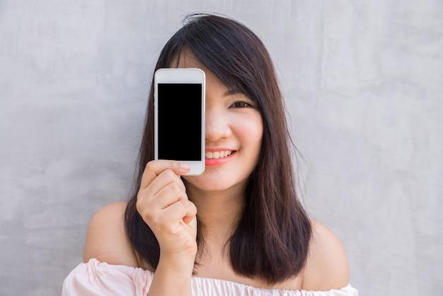 Femme souriante montrant un écran vierge sur un smartphone debout sur un mur en béton.