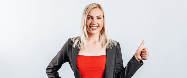 Femme souriante montrant les pouces vers le haut et regardant la caméra sur un mur blanc