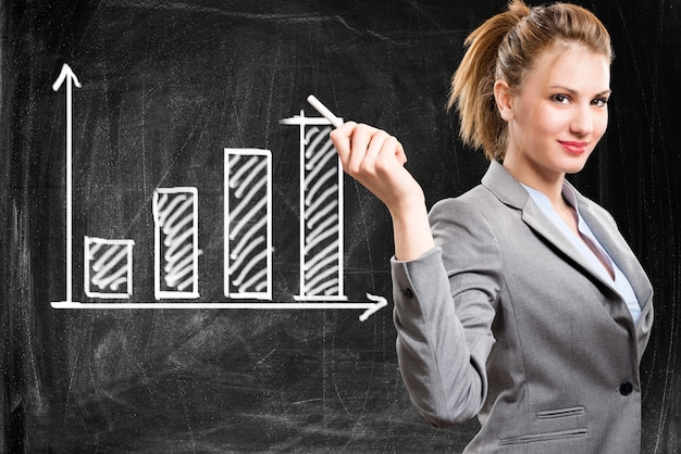 Femme souriante montrant une tendance commerciale positive sur un tableau noir