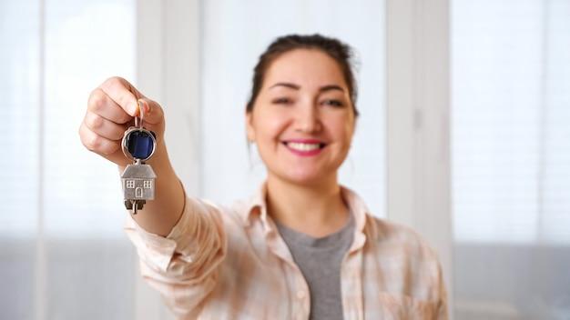 Une femme souriante montre des clés avec un breloque de maison près de la fenêtre