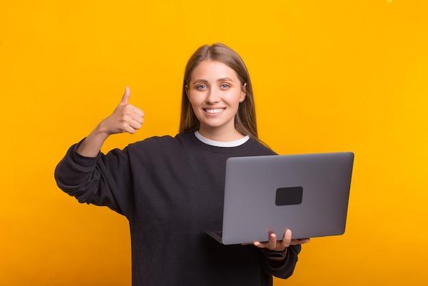 Une femme souriante montre le pouce vers le haut tout en tenant son ordinateur portable.