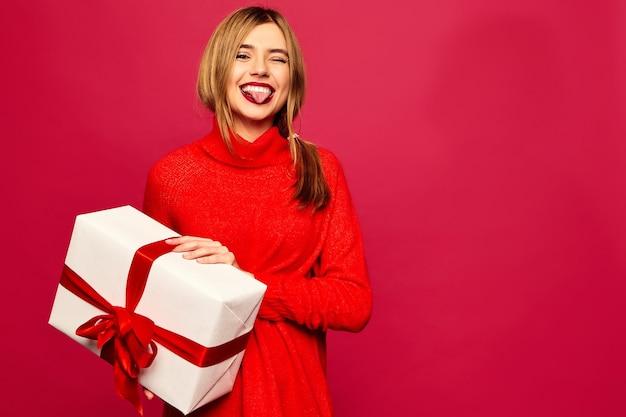 Femme souriante avec de nombreux coffrets cadeaux posant sur un mur rouge
