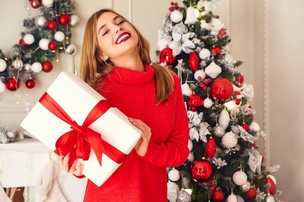 Femme souriante avec de nombreux coffrets cadeaux posant près de sapin de noël décoré