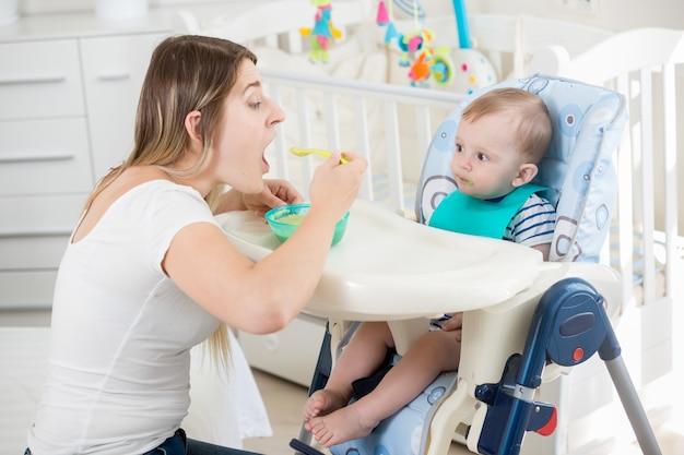 Femme souriante nourrir son petit garçon dans une chaise haute au salon