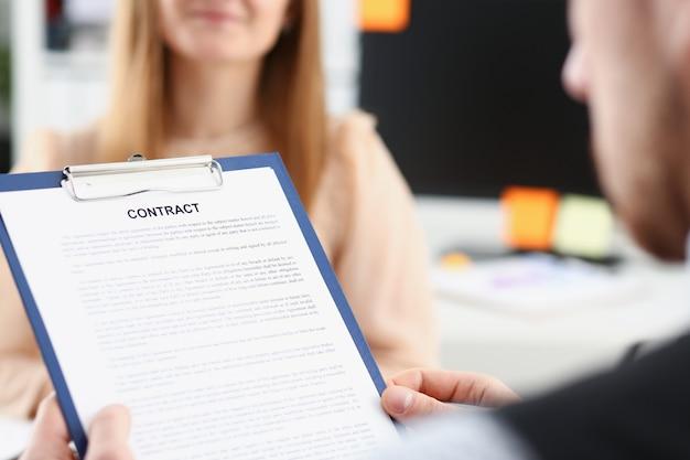 Femme souriante offre un formulaire de contrat sur le bloc-notes et un stylo argenté à signer