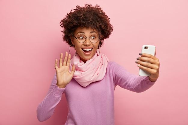 Une femme souriante optimiste dit bonjour enregistre un message vidéo, appelle via une application de médias sociaux sur un cellulaire, tient un gadget devant, agite la paume de la main, vêtue d'une tenue élégante