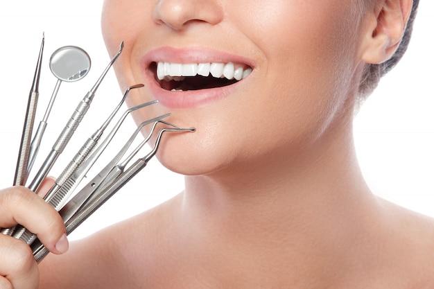 Femme souriante et outils dentaires