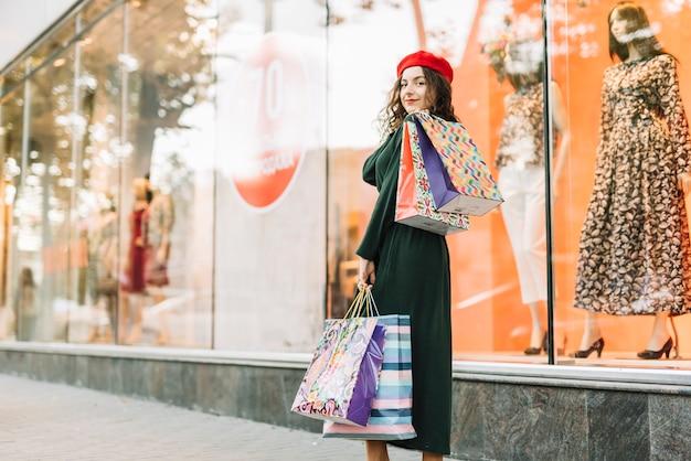 Femme souriante avec des paquets colorés au cas