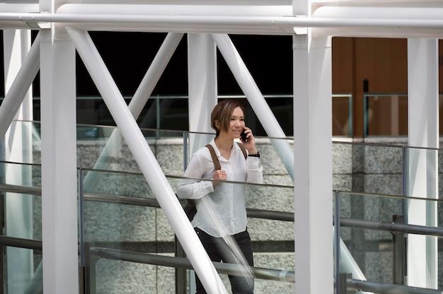 Femme souriante parlant au téléphone coup moyen