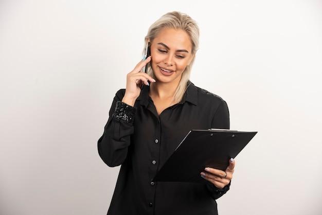 Femme souriante parlant au téléphone mobile et tenant un presse-papiers. photo de haute qualité
