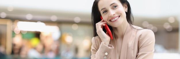 Femme souriante parlant sur smartphone alors qu'elle était assise dans un café