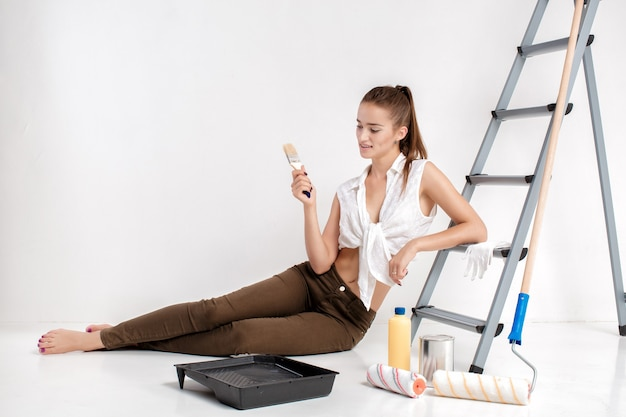 Femme souriante peinture mur dans sa maison. belle femme tenant un pinceau