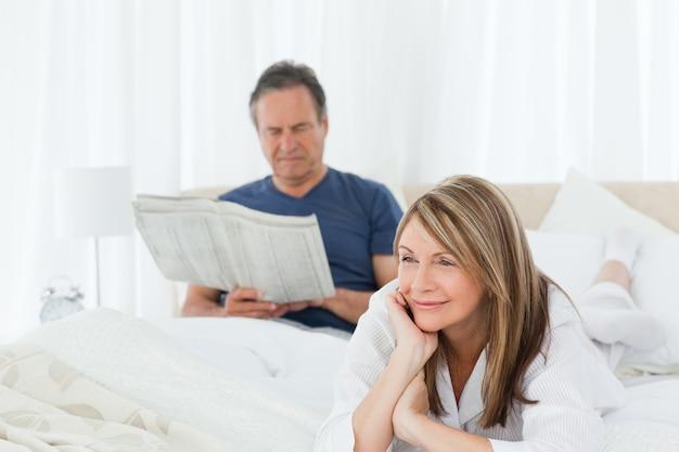 Femme souriante pendant que son mari lit