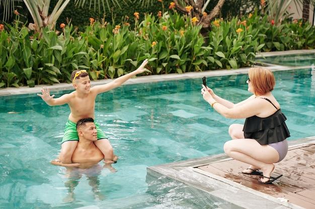 Femme souriante photographiant son fils préadolescent excité assis sur les épaules du père quand ils sont debout dans la piscine