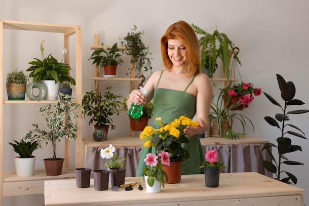 Femme souriante de plan moyen arrosant la fleur