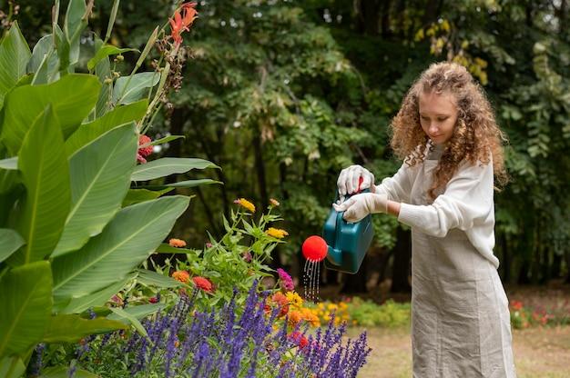 Femme souriante de plan moyen arrosant des fleurs