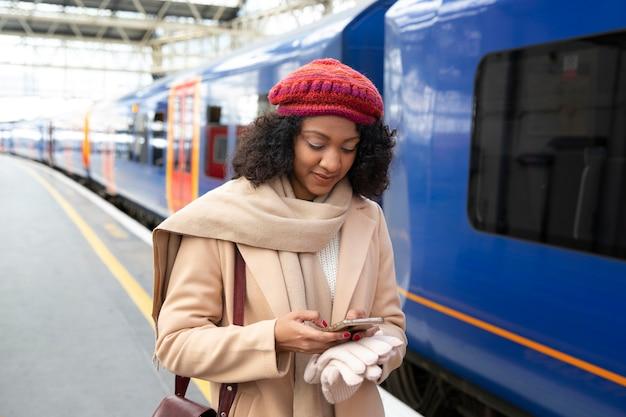 Femme souriante de plan moyen à la gare