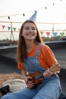 Femme souriante de plan moyen jouant de la musique