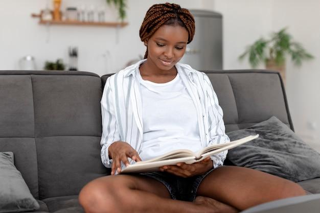 Femme souriante de plan moyen lisant sur un canapé