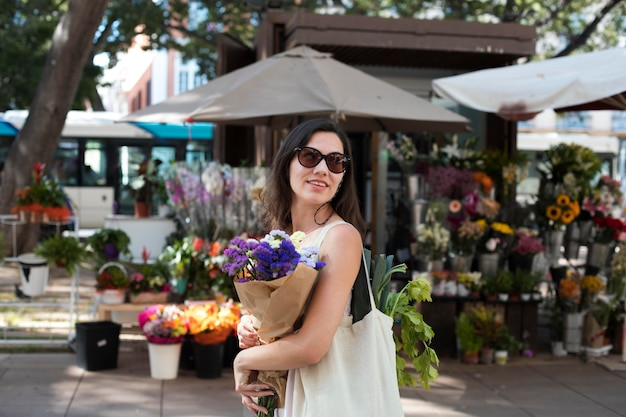 Femme souriante de plan moyen portant un bouquet