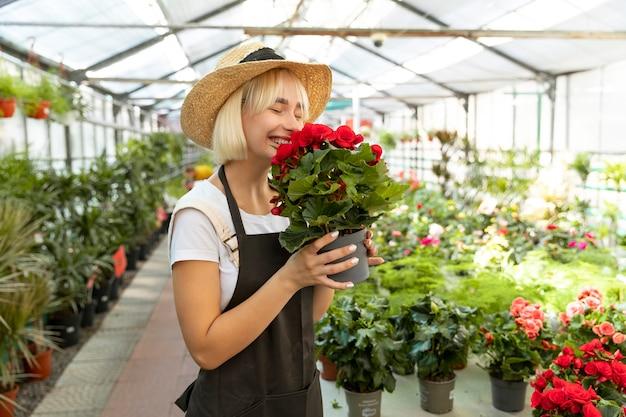 Femme souriante de plan moyen sentant des fleurs