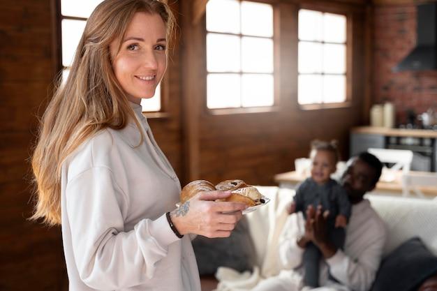 Femme souriante de plan moyen tenant de la nourriture