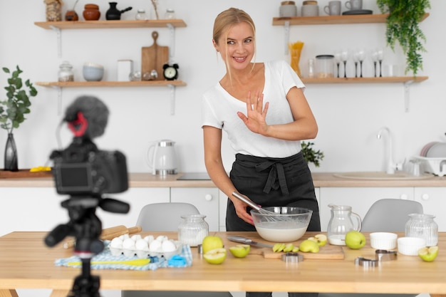 Femme souriante de plan moyen en train de cuisiner