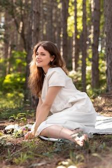 Femme souriante de plein coup assise sur une couverture