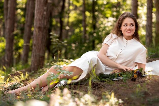 Femme souriante de plein coup posant dans la nature