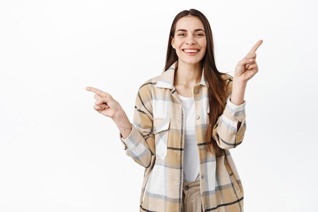 Femme souriante pointant sur le côté avec une expression de visage heureux, fond blanc.