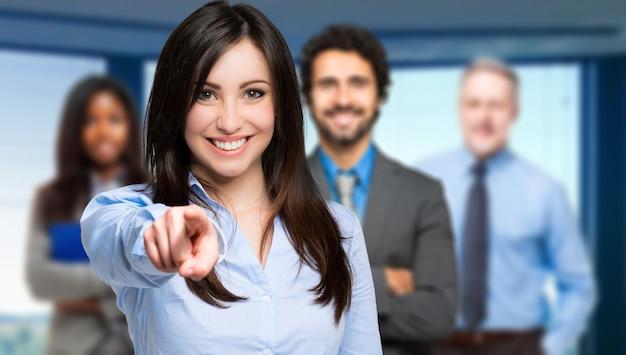 Femme souriante pointant son doigt vers vous