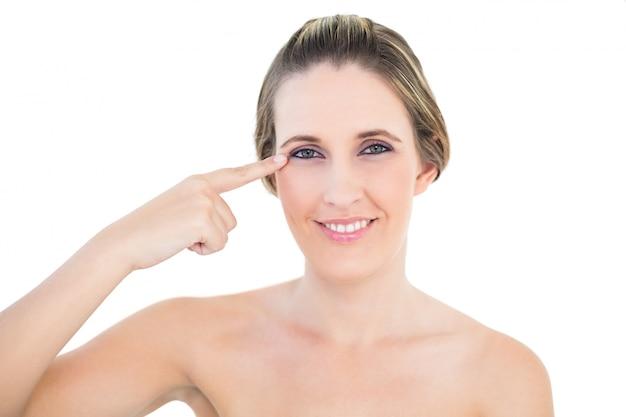 Femme souriante pointant son oeil